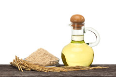 Rice bran oil. In bottle glass with seed and bran on the old plank wood Stock Photography