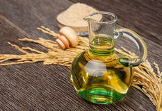 Rice bran oil. In bottle glass with seed and bran on the old plank wood Stock Photos