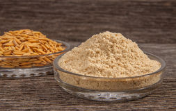 Rice bran and Paddy. In dish on the old plank wood Royalty Free Stock Photo