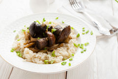 Rice with Brown cap boletus and cream on a white plate. Closeup Stock Image