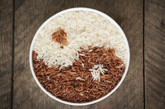 Rice. Brown rice and white rice in cup have wood table is backgruond Royalty Free Stock Image