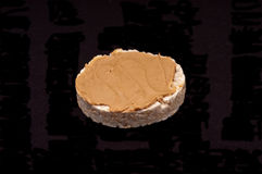 Rice cake with peanut butter. Single rice cake topped with peanut butter Royalty Free Stock Images