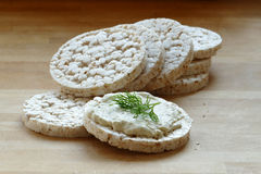 Rice cakes, one with cream cheese and herbs on a wooden board Stock Photo
