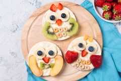 Rice cakes with yoghurt and fresh fruits in a shapes of cute owls on a wooden board, meal for kids idea, top view