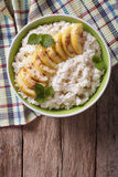 Rice with caramelized apples in a bowl. vertical top view Stock Image