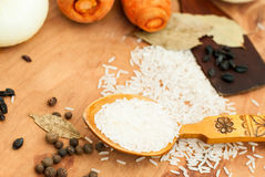 Rice, carrot, onion, spices, barberry on a table set for pilaf Stock Photo