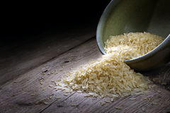 Rice in a ceramic bowl on old wood, dark background Royalty Free Stock Photography