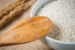 Rice cereal and wooden spoon on burlap background Royalty Free Stock Photos