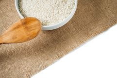 Rice cereal and wooden spoon on burlap background Royalty Free Stock Photo