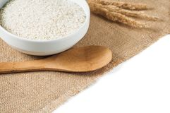 Rice cereal and wooden spoon on burlap background Royalty Free Stock Image
