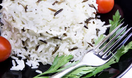 Rice with cherry tomatoes and greens on a black plate. Dish of black and white rice royalty free stock image
