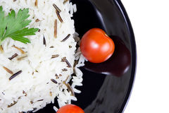 Rice with cherry tomatoes and greens on a black plate. Dish of black and white rice royalty free stock images