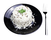 Rice with cherry tomatoes and greens on a black plate. Dish of black and white rice stock photo
