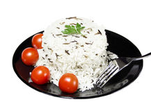 Rice with cherry tomatoes and greens on a black plate. Dish of black and white rice stock images