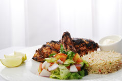 Rice with chicken. Fresh and tasty vegetable rice with grilled chicken in a white plate Royalty Free Stock Image