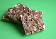Rice chocolates. Three square pieces of rice chocolates on green background Stock Image