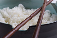Rice and chopsticks. Bowl of white rice with chopsticks lying on top Stock Images
