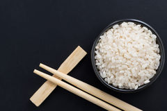 Rice and chopsticks for sushi on a black background, top view Stock Image