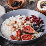Rice coconut porridge with figs, berries, nuts, dried apricots and coconut milk in plate on rustic wooden background. Healthy breakfast ingredients. Clean stock images