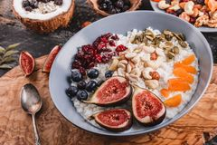 Rice coconut porridge with figs, berries, nuts, dried apricots and coconut milk in plate on rustic wooden background. Healthy. Breakfast ingredients. Clean royalty free stock image