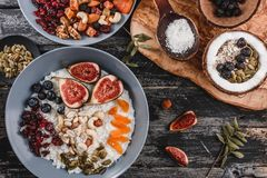 Rice coconut porridge with figs, berries, nuts, dried apricots and coconut milk in plate on rustic wooden background. Healthy. Breakfast ingredients. Clean stock image
