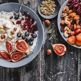 Rice coconut porridge with figs, berries, nuts, dried apricots and coconut milk in plate on rustic wooden background. Healthy breakfast ingredients. Clean stock photo