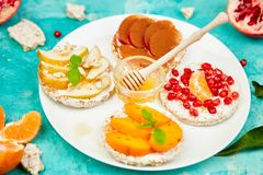 Rice Crisp bread healthy snack with tropical fruit. Pomegranate, tangerine, persimmon, apple. Easy breakfast close-up on a blue background. Summer vegan, diet stock photos
