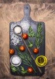 Rice, czereśniowi pomidory, rozmaryny i ziele, drewniana łyżka, pikantność na tnącej desce na drewnianym nieociosanym tło odgórne zdjęcia royalty free