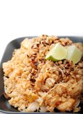 Rice dish. Close-up of asian rice dish served on black plate, isolated on white background Stock Image