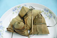 Rice dumpling. Steamed Chinese rice dumplings (zongzi) wrapped in bamboo leaves, filled with glutinous/sticky rice, pork, mushrooms, and peanuts. These are eaten Royalty Free Stock Photos