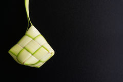 Rice Dumpling Casing or Ketupat. Rice dumpling casing or also know as ketupat made from coconut palm leaf on black background. Ketupat is a type of dumpling made Royalty Free Stock Photo