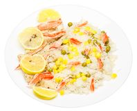 Rice with fish, shrimp, peas, corn and lemon on a white plate. I. Solate white background Royalty Free Stock Image