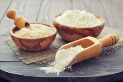Rice flour. Raw rice and flour in bowls with scoop on wooden background royalty free stock image