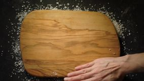 Rice frame. Woman`s hands making a frame from long white bamati rice on a black cement background around the cutting board, then remove it and put on three stock footage