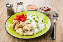 Rice, fried chicken meat and sweet pepper, spices, sauces. Plate with rice, fried chicken meat and sweet pepper, spices, sauces and fork on wooden table Royalty Free Stock Photography