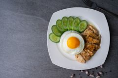 Rice,Fried egg,Fried chicken with garlic and black pepper in white dish on the concrete table royalty free stock image