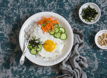 Rice with fried egg, pickled carrots, cucumber and seaweed. Healthy diet food concept. Royalty Free Stock Image