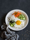 Rice with fried egg, pickled carrots, cucumber and seaweed. Healthy diet food concept. Top view Stock Photography