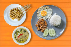 rice with fried pork with garlic, fried egg and Thai green curry Royalty Free Stock Image