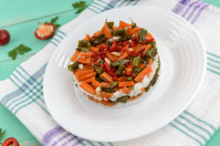 Rice and fried vegetables asparagus beans, carrots - vegan diet garnish. Decorated layers of salad on a white plate Royalty Free Stock Photo
