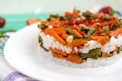 Rice and fried vegetables (asparagus beans, carrots) - vegan diet garnish. Decorated layers of salad on a white plate. Close up Royalty Free Stock Image