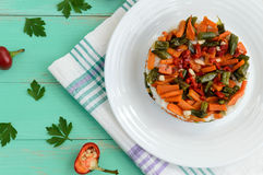 Rice and fried vegetables asparagus beans, carrots - vegan diet garnish. Decorated layers of salad on a white plate. The top view Royalty Free Stock Photography