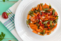 Rice and fried vegetables asparagus beans, carrots - vegan diet garnish. Decorated layers of salad on a white plate. Royalty Free Stock Photo
