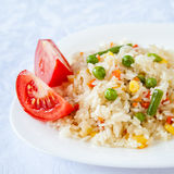 Rice with fried vegetables served with fresh tomato. On white plate Stock Images