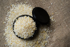 Rice grain. Rice in black wood container on the sack Stock Photography