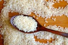 Rice grain in dark wooden spoon Stock Photography