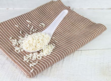 Rice grain in white spoon on a napkin Stock Photography
