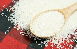 Rice grain and wooden spoon Stock Images