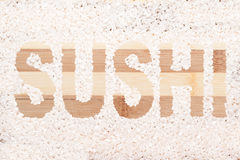 Rice grain. Word sushi written on wooden cutting board Royalty Free Stock Photo