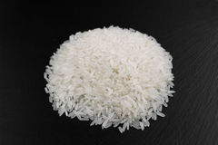 Rice grains on a black background. Hill rice grains on a black background, close-up Stock Images